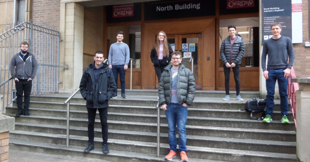 seven of the 14 students in Cohort 2 outside North Building socially distanced